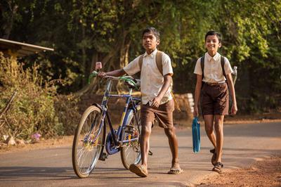 Indische Kinder auf dem Schulweg, einer schiebt ein Fahrrad.