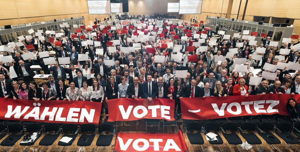 """Kongress-Saal, in dem viele Teilnehmer zur Wahl aufrufen. Transparente im Vordergrund mit """"Wählen"""", """"Vote"""", """"Votez"""", """"Vota""""."""