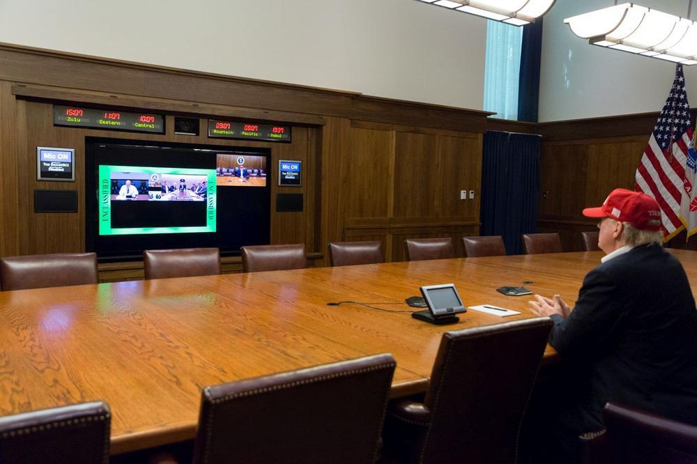 Donald Trump folgt einer Videoübertragung, allein an einem langen Konferenztisch.