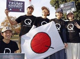 """5 Japaner mit Q auf T-Shirts und """"17"""" auf Baseball-Kappen halten eine kleine weiße Fahne vor sich, auf der auch Q steht."""
