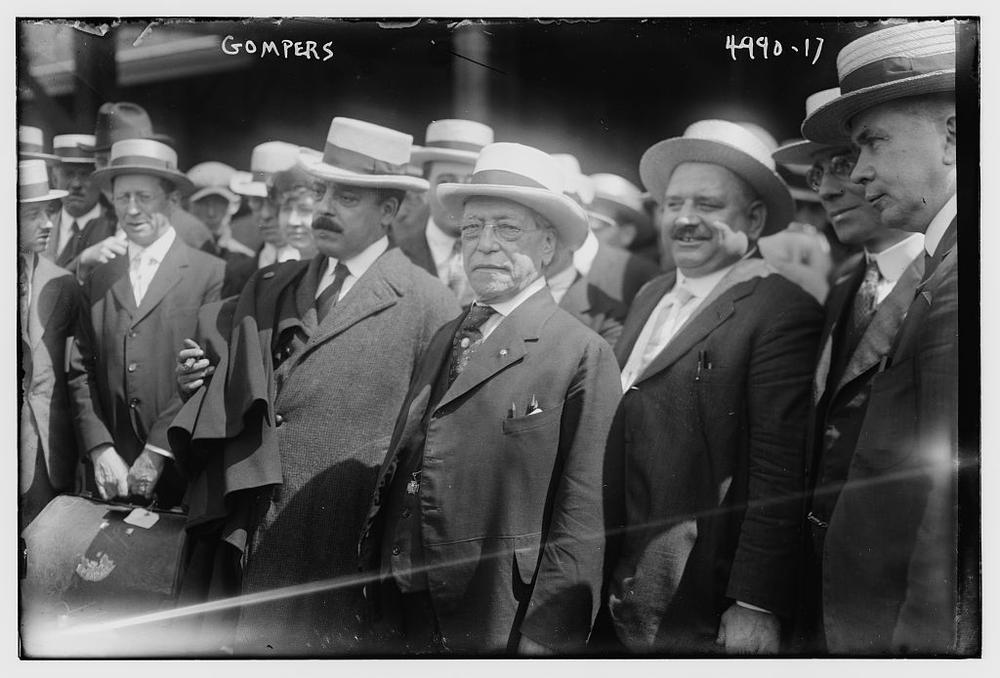 Samuel Gompers auf einem alten Schwarzweißbild mit einer Gruppe von Männern. Alle tragen altmodische Anzüge und Strohhüte
