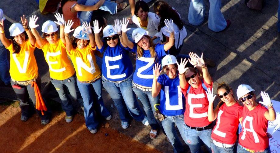 Nebeneinander stehen Frauen und die Buchstaben auf ihren bunten T-Shirts ergeben zusammen das Wort Venezuela.