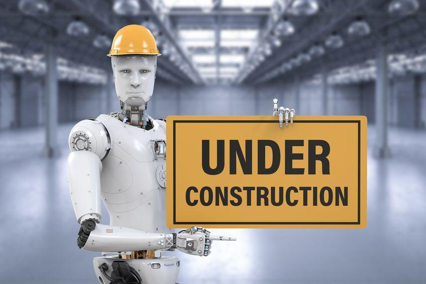 """Ein Roboter mit gelbem Schutzhelm steht in einer leeren Industriehalle und hält ein Schild, auf dem """"Under Construction"""" steht."""
