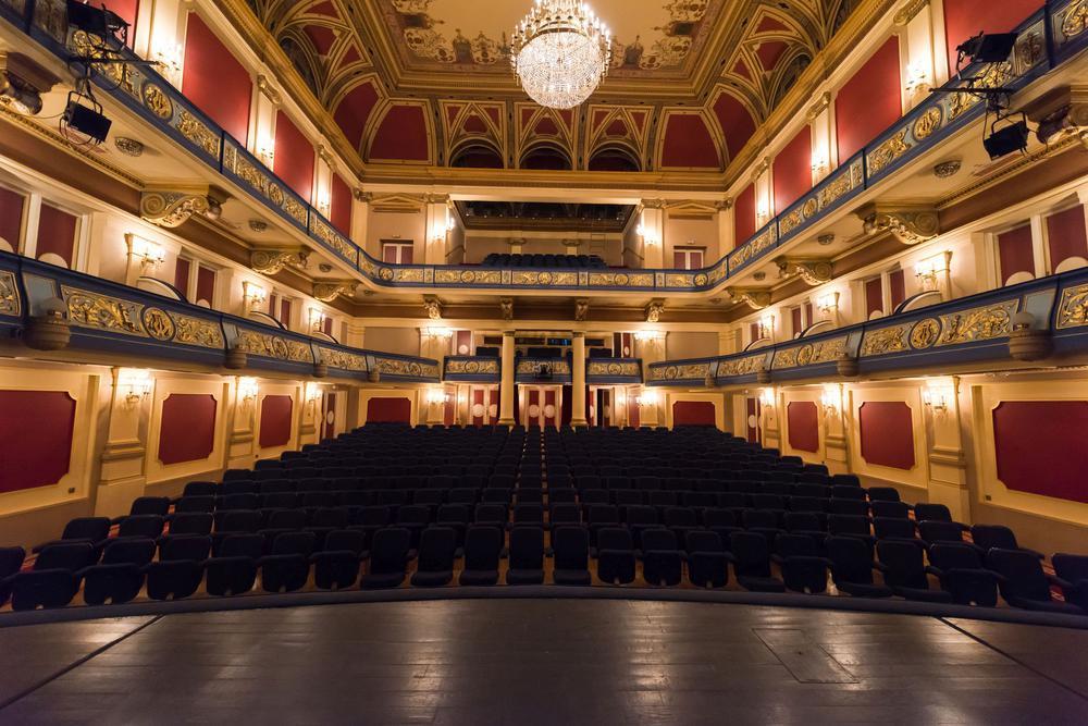 Blick in ein leeres Theater von der Bühne aus. Der Raum ist in rot gehalten.