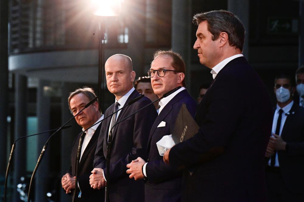 Vier Männer in dunklen Anzügen stehen mit etwas Abstand nebeneinander, vor sich Mikrofone, und blicken ernst in Kameras.