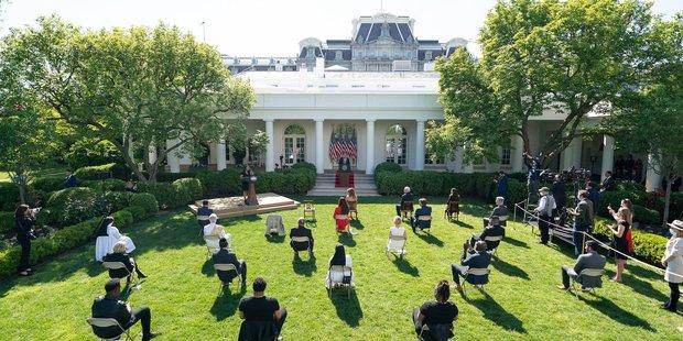 Im Rosengarten des Weißen Haus (im Hintergrund) sitzen vereinzelt auf Klappstühlen Menschen. Vor dem Gebäude steht der Präsident an einem Rednerpult.