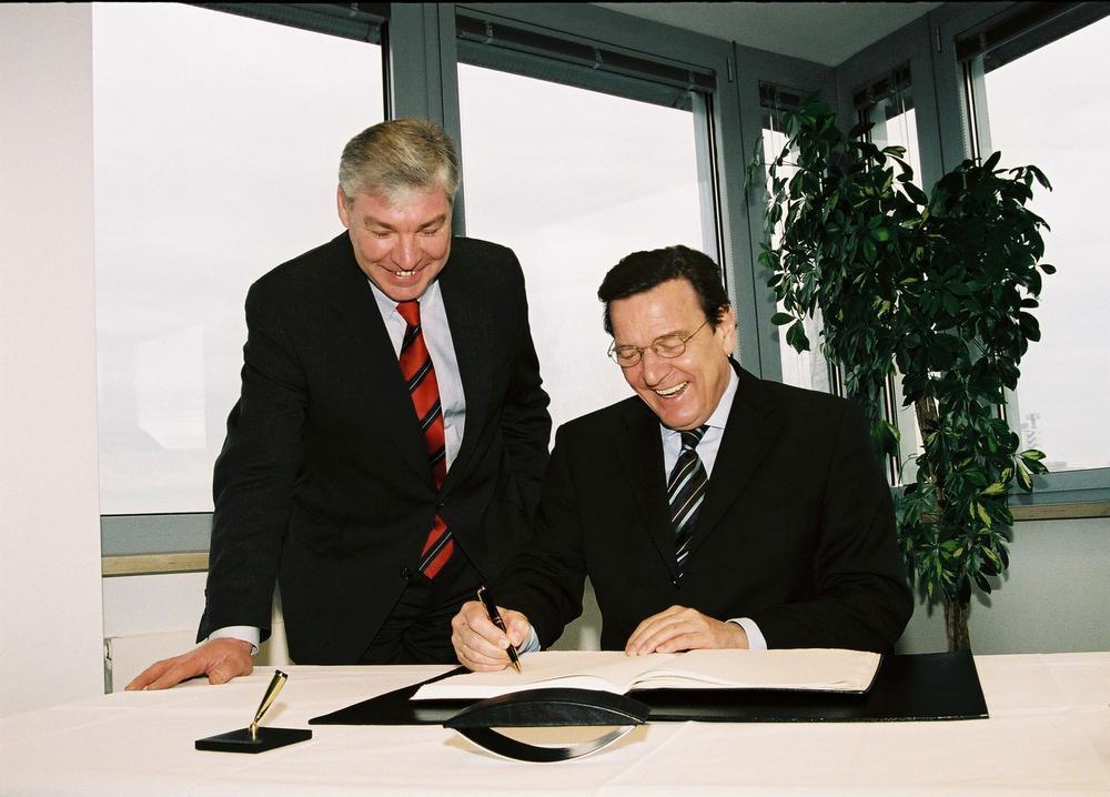 Gerhard Schröder sitzt an einem Tisch und unterschreibt ein Dokument, Michael Sommer steht links neben ihm und schaut leicht vornübergebeugt zu.