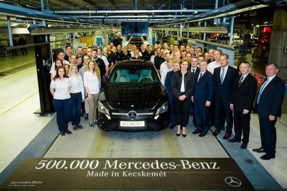 Mitarbeiterinnen und Mitarbeiter stehen am Ende einer Produktionsstraße im Autowerk rund um einen Mercedes.