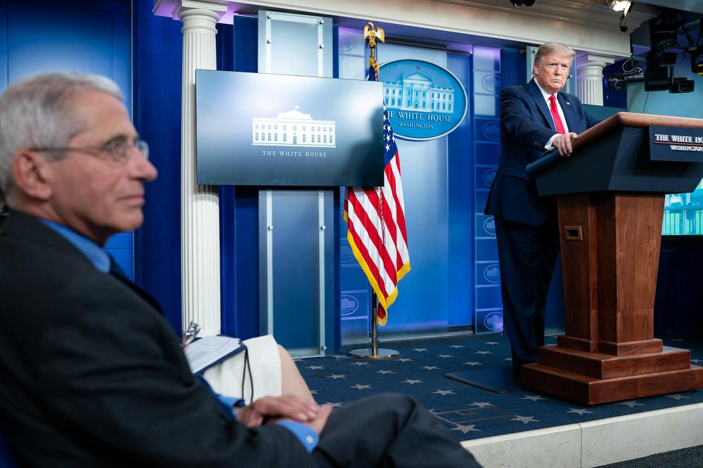 Donald Trump steht am Rednerpult im Presseraum des Weißen Hauses. Das Bild ist von der linken Seite des Raumes vorbei an Dr. Fauci aufgenommen.