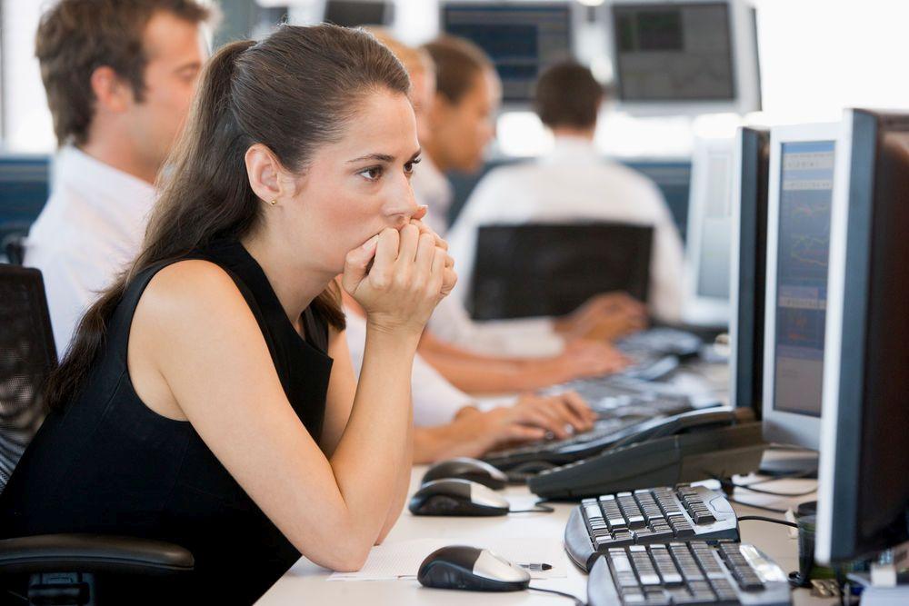 Junge Frau von der Seite aufgenommen, in einem Großraumbüro mit einigen Kollegen unscharf im Hintergrund, blickt besorgt auf ihren Computerbildschirm.