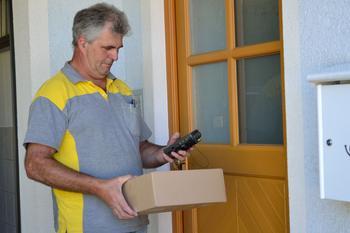 Paketbote mit Paket vor einer verschlossenen Haustür.