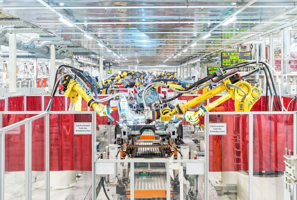 Fließband mit Robotern, die einen VW zusammenschweißen.
