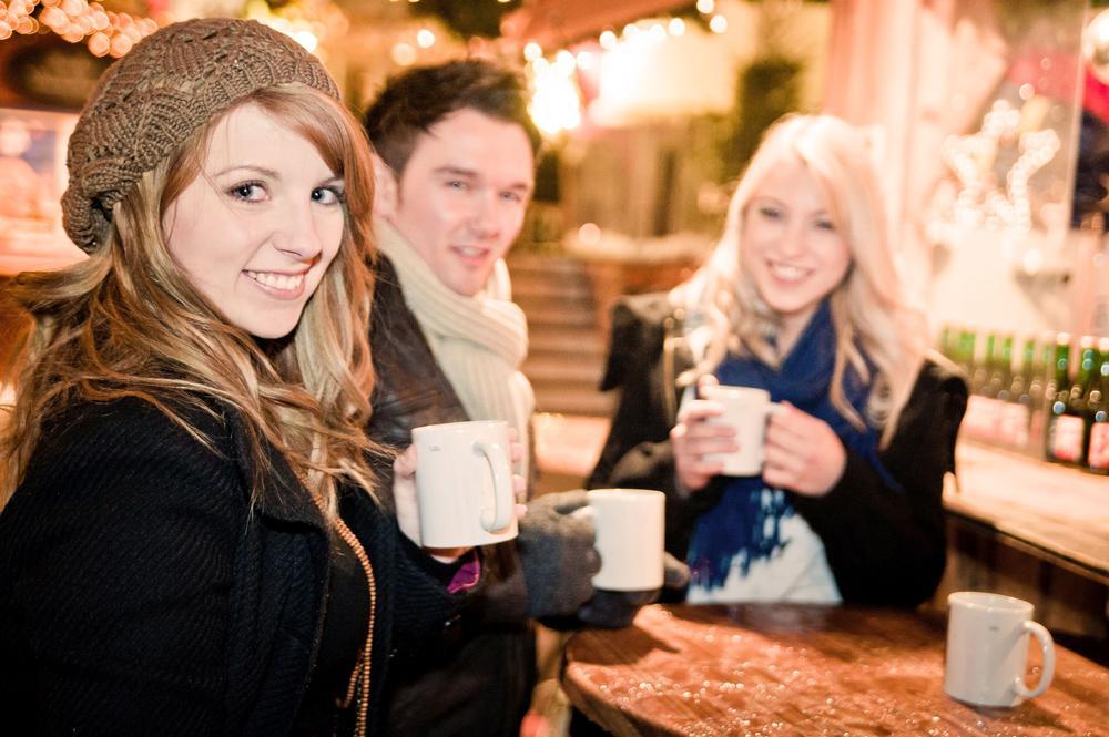 Zwei Frauen und ein Mann trinken Punsch auf einem Weihnachtsmarkt.