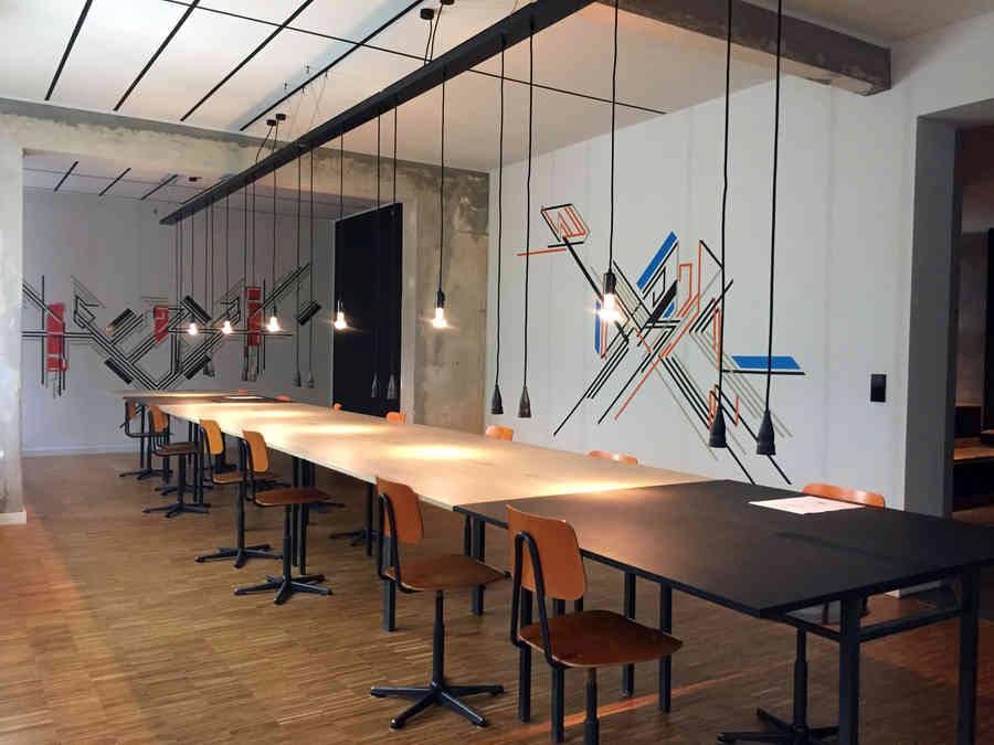 Ein etwa 8 Meter langer langer Tisch, an dem rechts und links Drehstühle stehen.