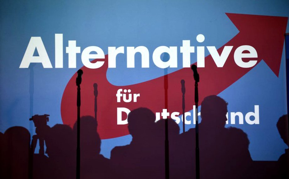 """Eine blaue Wand, auf der """"Alternative für Deutschland"""" steht, mit Schatten von mehreren Personen und zwei Mikrophonen."""