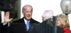Joe Biden hebt die rechte Hand zum Schwur, ihm gegenüber, von hinten zu sehen, steht ein Mann in schwarzer Richterrobe.