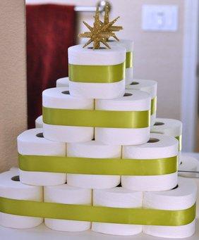 Toilettenpapierrollen so aufgestapelt, dass sie aussehen wie ein Baum. Obendrauf ist ein goldener Stern gesteckt.