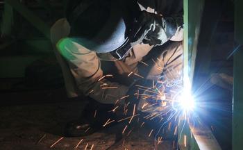 Ein Arbeiter schweißt an einem Stahlträger.