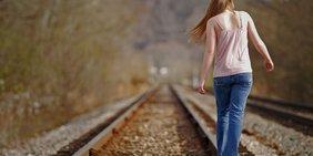 Ein Mädchen läuft auf verlassen Bahngleisen.