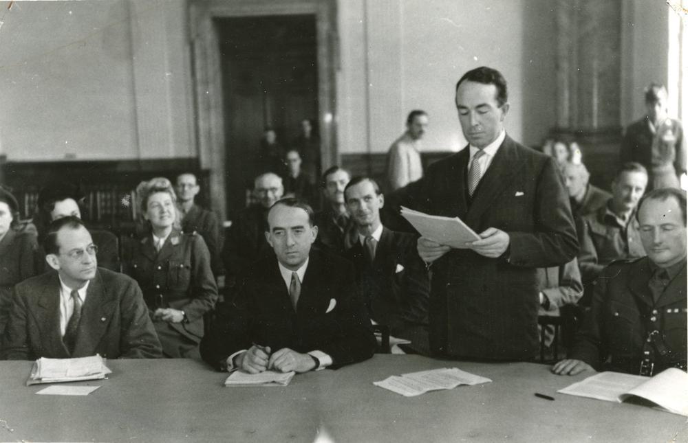 Schwarzweißbild von mehreren Männern, die hinter einem Tisch sitzen; einer steht und trägt etwas vor, das er von einem Blatt abliest, das er in der Hand hält.