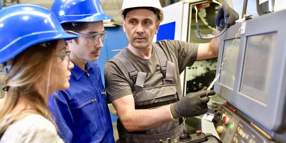 Zwei Auszubildende, eine junge Frau und ein junger Mann, mit blauen Helmen folgen den Erklärungen eines älteren Mannes, der auf zwei Monitore weißt.