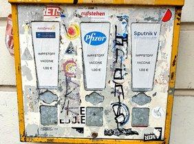 Kaugummiautomat mit drei Fächern, auf den von links nach rechts die Namen der Impfstoffe geklebt wurden: AstraZeneca, Pfizer, Sputnik V.