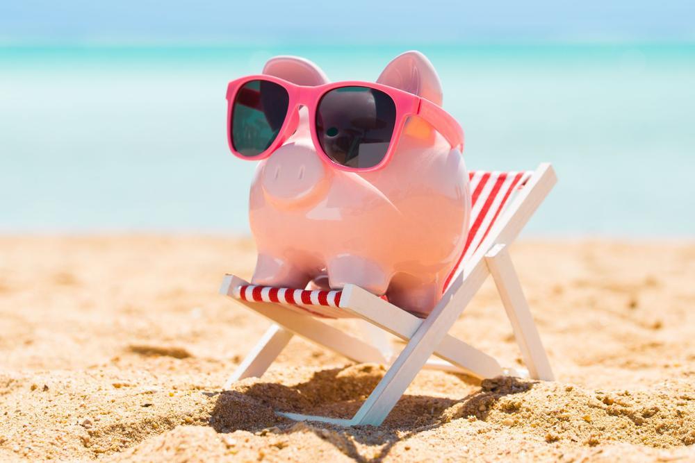 Rosa Plastikschwein auf einer Sonnenliege mit rosa Sonnenbrille.