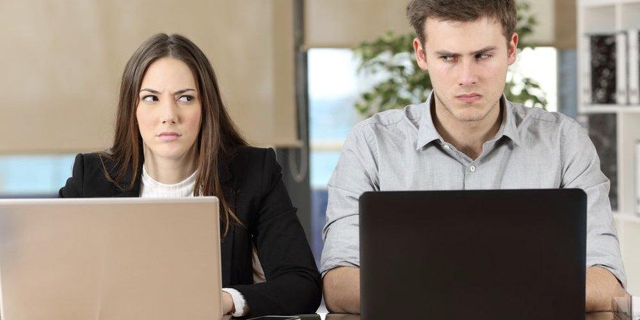 Eine Frau und ein Mann sitzen nebeneinander an einem Tisch hinter ihren Labtops und schielen jeweils zur Seite, zu dem anderen.