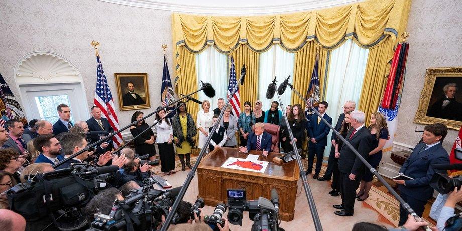 Mikrophone und Kameras sind auf Donald Trump gerichtet, der im Oval Office des Weißen Hauses an seinem Schreibtisch sitzt.
