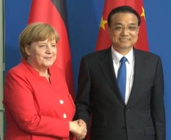 Chinas Premier Li Keqiang und Angela Merkel beim Handschlag vor deutscher und chinesischer Flagge.