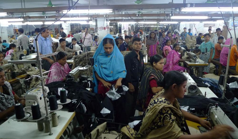 Eine Textilfabrik mit vielen Näherinnen, die dicht an dicht sitzen und arbeiten. Einige blicken in die Kamera