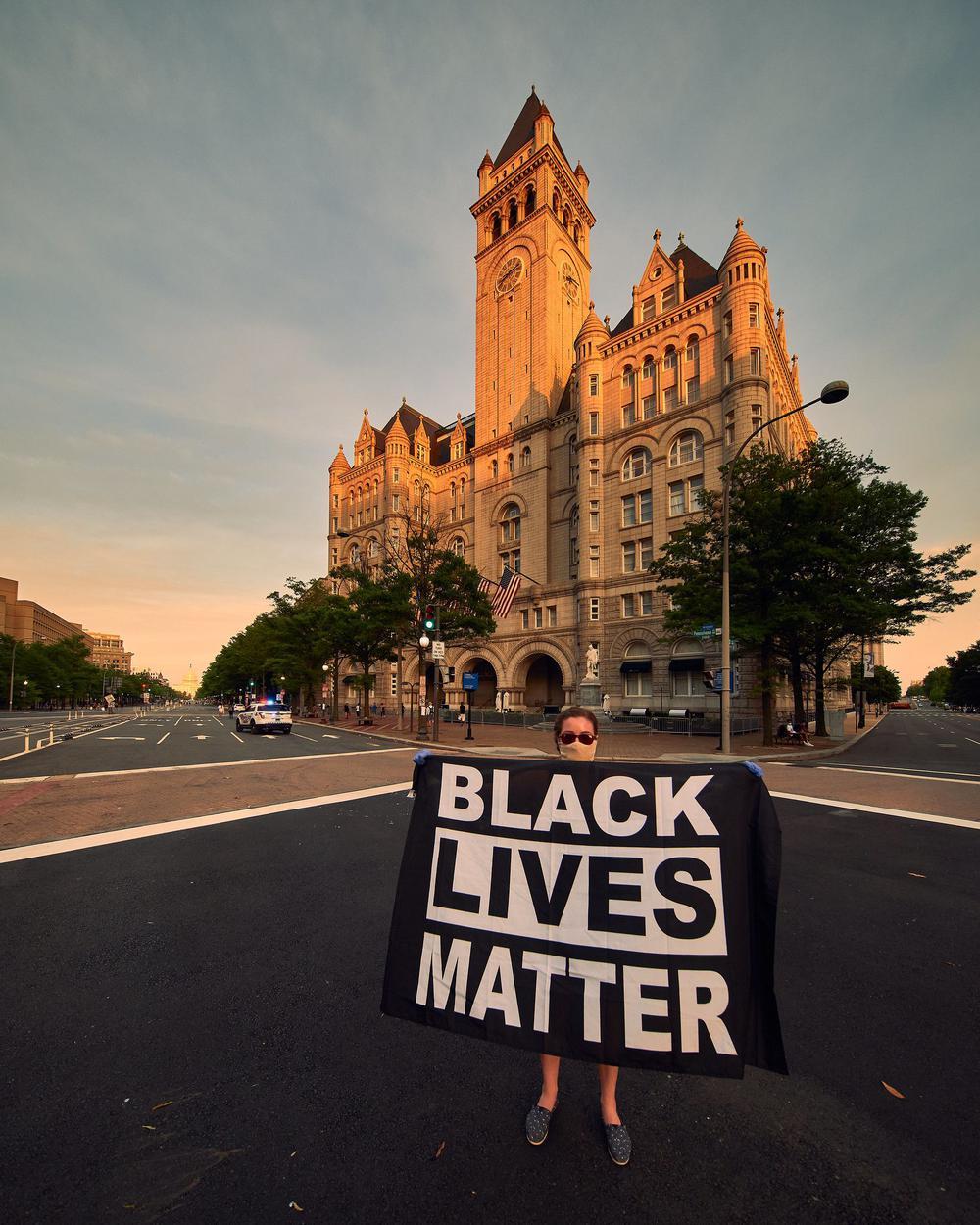 Eine Demostrantin steht auf einer leeren Kreuzung und hält ein schwarzes Transparent vor sich mit der Aufschrift: Black Lives Matter.