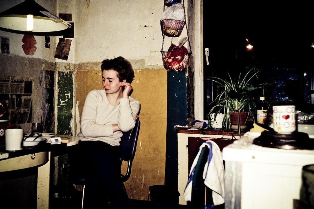 Eine Frau sitzt an einem Küchentisch, die Wände sind unverputzt, es sieht sehr ärmlich aus.