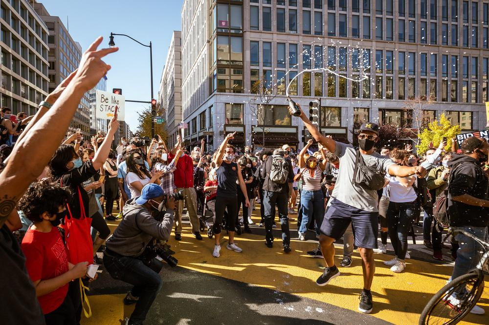 Menschen feiern auf der Straße, Sekt spritzt in die Höhe, US-Flaggen werden geschwenkt, strahlender Sonnenschein.