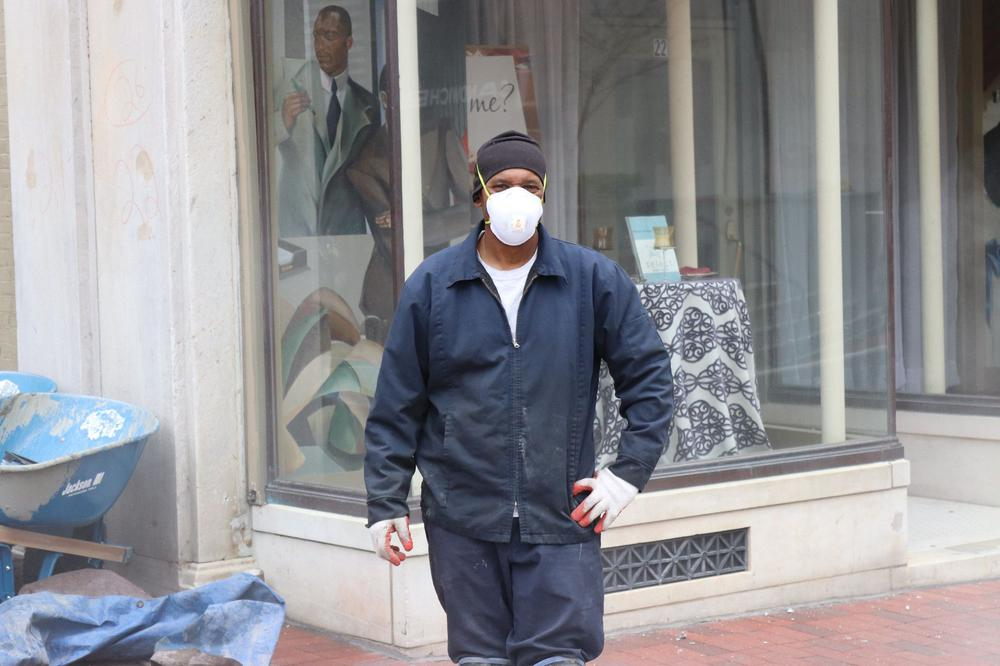Arbeiter in Blaumann und mit Atemschutzmaske steht auf der Straße, nicht weit neben ihm eine Schubkarre, im Hintergrund ein Kleidungsgeschäft.