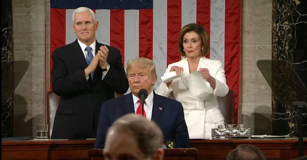 Präsident Trump steht im Kongress am Rednerpult, hinter ihm etwas höher Vizepräsident Pence und die Sprecherin des Abgeordnetenhauses Nancy Pelosi, die Papier zerreißt.