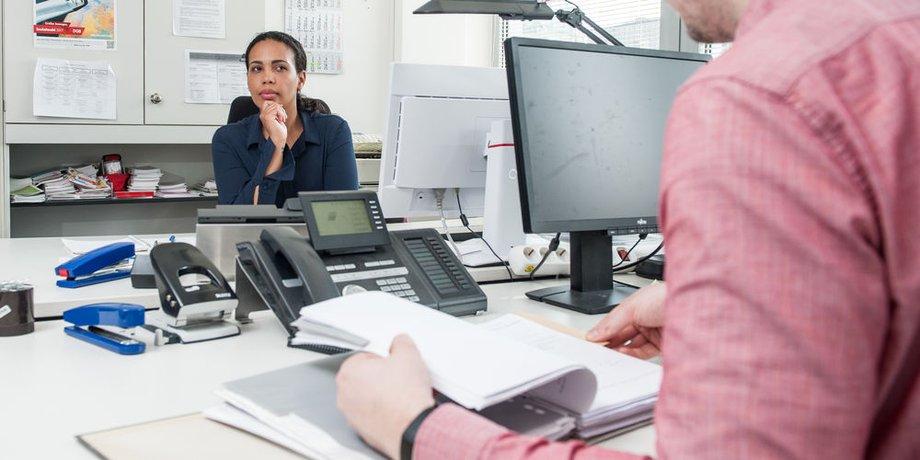 Eine Frau am Schreibtisch blickt skeptisch auf ihren Kollegen gegenüber.
