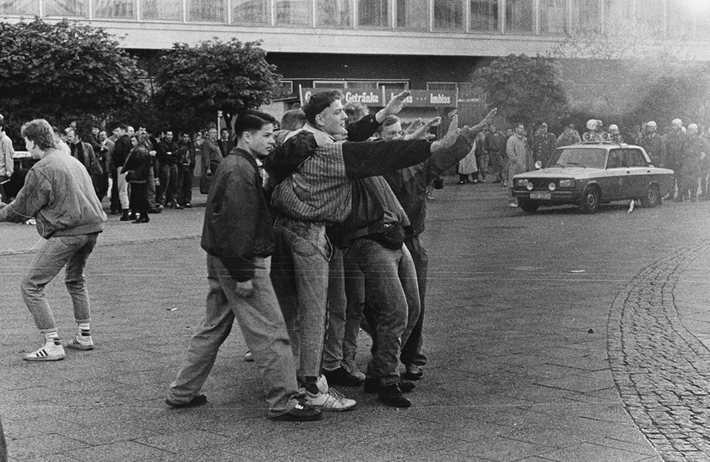 Junge Männer stehen in einer Rauchwolke und zeigen den Hitlergruß. Foto in Schwarzweiß.