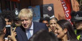 Boris Johnson in einer Menschenmenge, in der im Vordergrund ein Mann ein Handyfoto von ihm macht