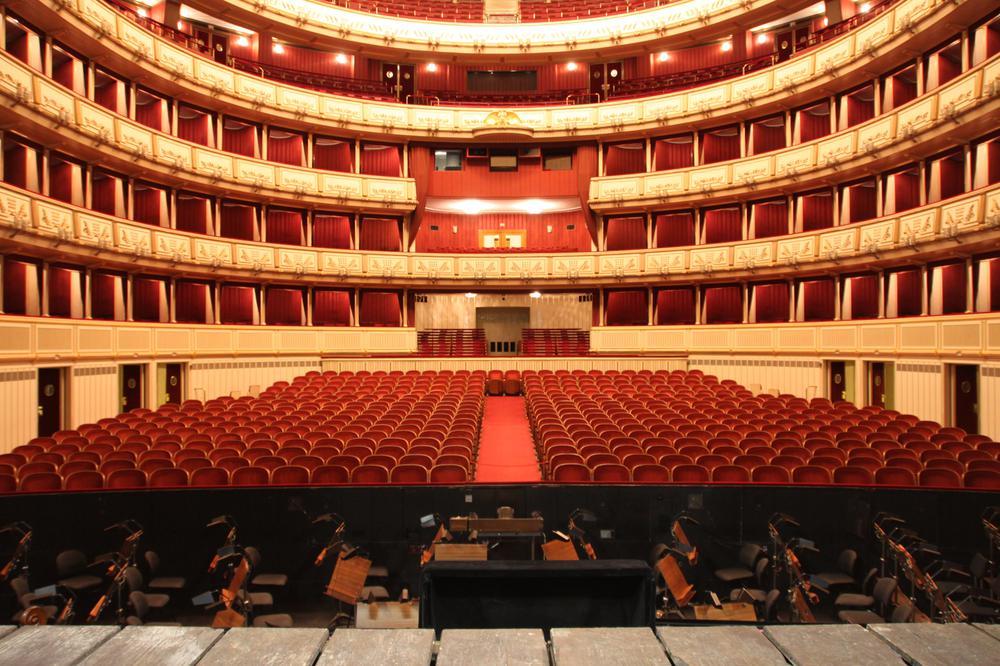 Der leere Zuschauerraum einer barock wirkenden Oper mit roten Sitzen und goldfarbenen Balkonen.