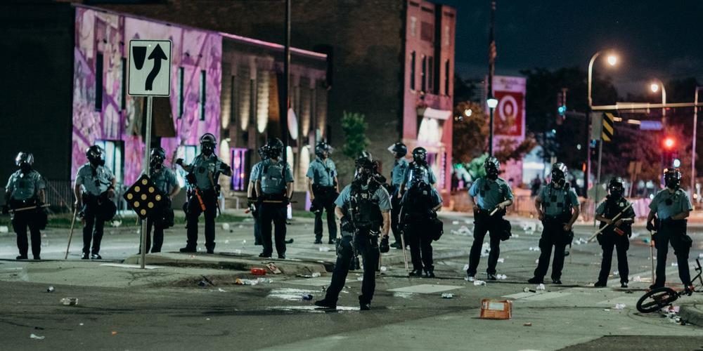 Polizisten stehen nebeneinander in Kampfkleidung und riegeln nachts eine Straße ab. Es ist eine bedrohlich wirkende Kulisse.