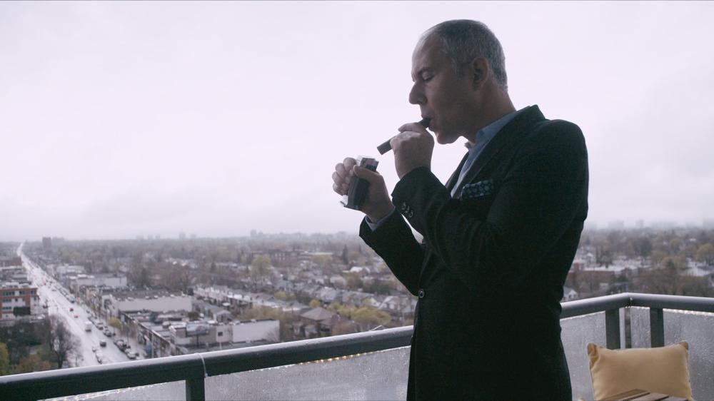 Ein Mann auf einem Balkon mit Blick über eine Stadt (Toronto) zündet sich eine Zigarre an.