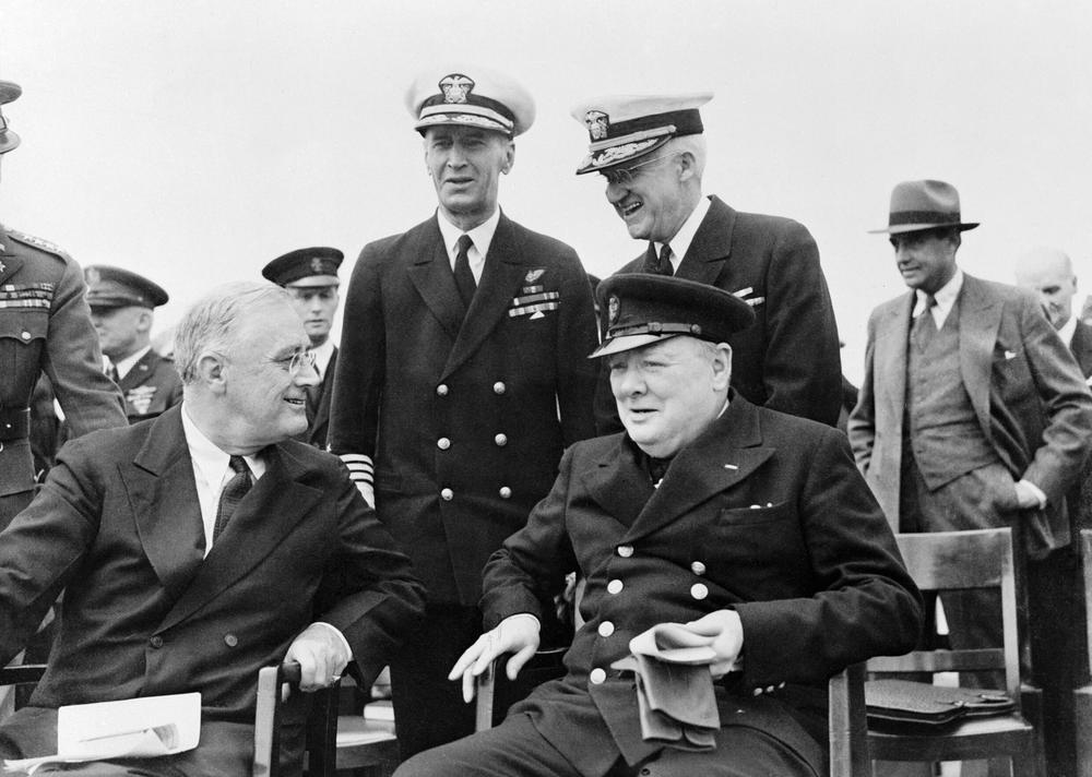 Winston Churchill und Franklin D. Rooesevelt sitzen auf Holzstühlen und unterhalten sich. Hinter ihnen stehen hochrangige Militärs in Uniform.