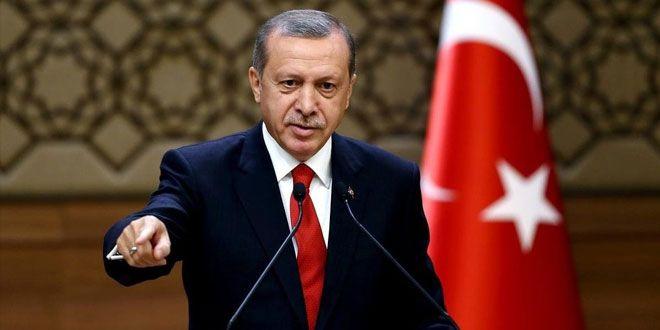 Erdogan bei einer Rede an einem Pult mit Mikrofon vor einer türkischen Fahne.