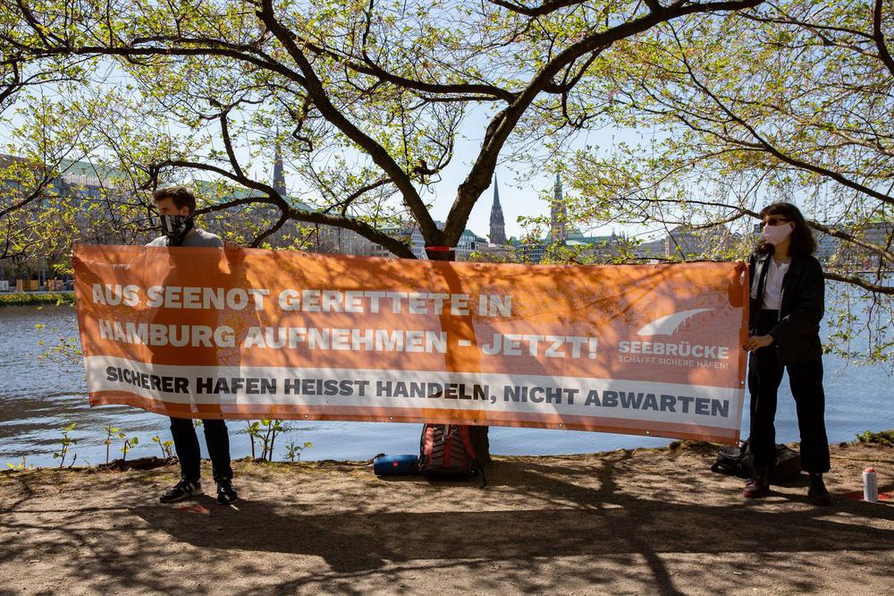 Zwei Protestierende stehen mit zwei Meter Abstand nebeneinander und halten zwischen sich ein Transparent. Sie tragen Atemschutzmasken und stehen vor Bäumen am Elbufer.