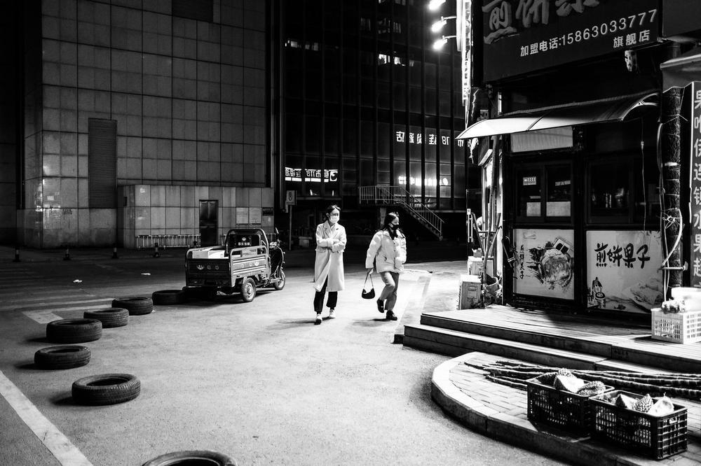 Zwei Frauen mit Atemmasken überqueren eine kleine sonst menschenleere Straße in China, um zu einem Geschäft zu gelangen.