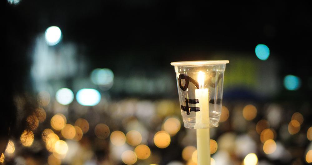 Menschen halten Kerzen hoch. Im Vordergrund ist eine Kerze scharf zu erkennen, die anderen Kerzen im Hintergrund sind nur als unscharfe Lichtkegel zu sehen.