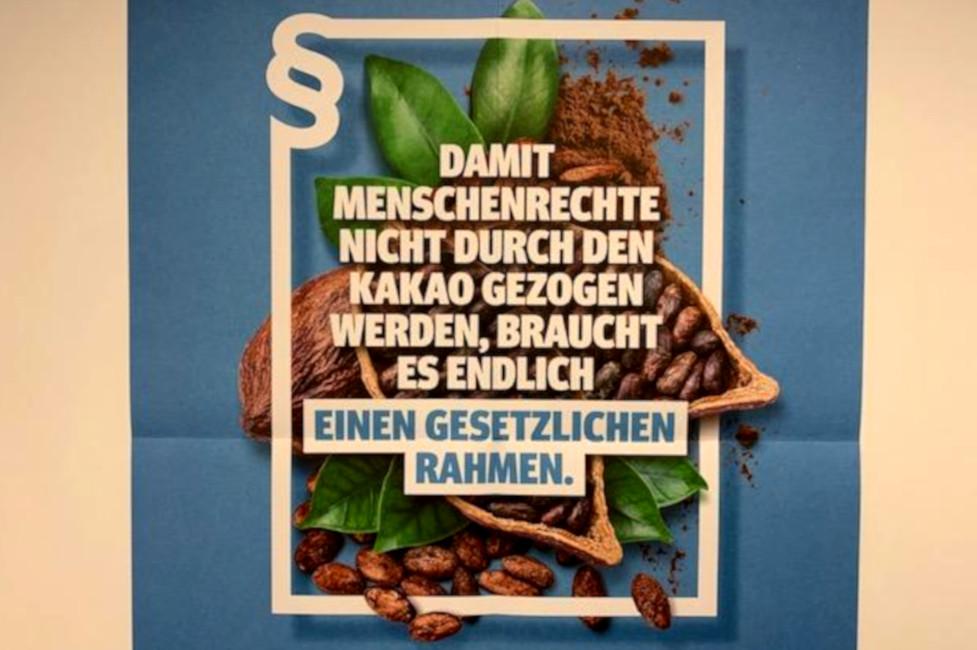 """Blaues Plakat zur Lieferketteninitiaver mit dem Text  in einem Bilderrahmen: """"Damit Menschenrechte nicht durch den Kakao gezogen werden, braucht es endlich einen gesetzlichen Rahmen""""."""