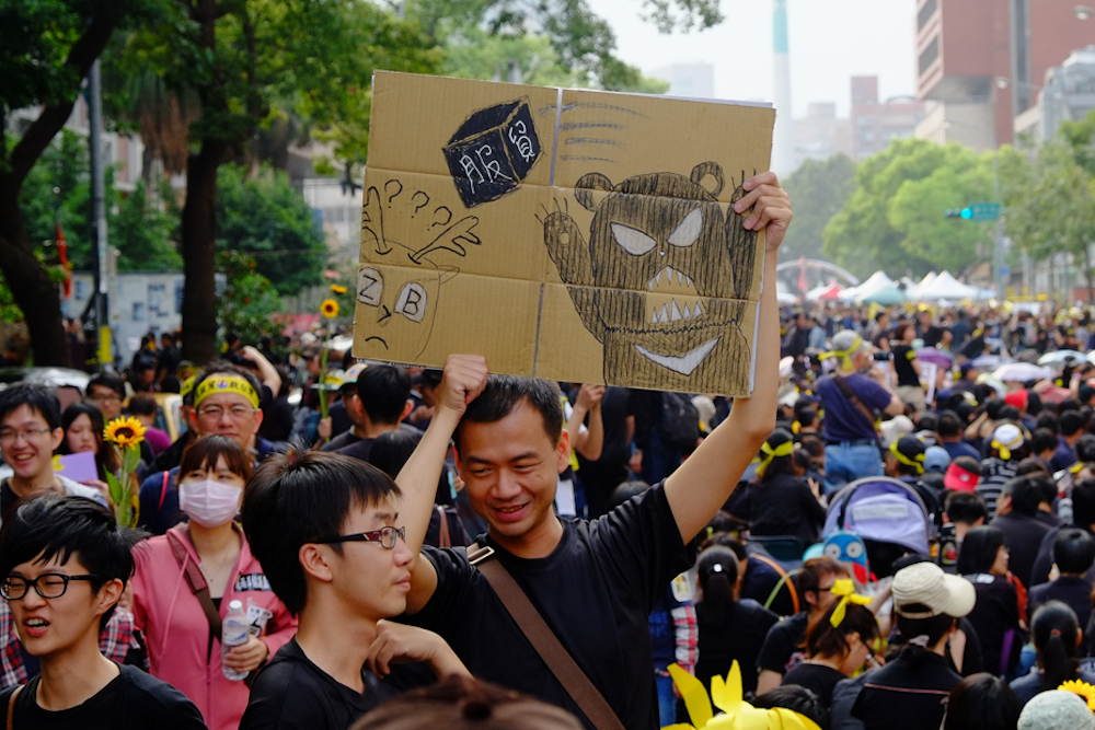 Protestierende marschieren in Taiwan. Einige tragen Gesichtsmasken