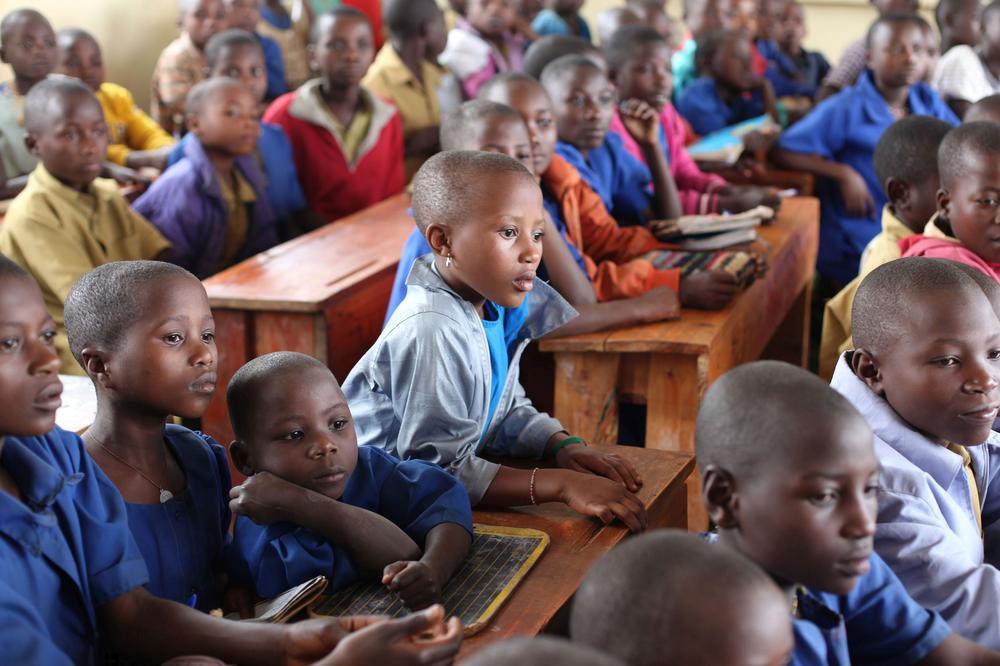Eine große Schulklasse in Nigeria mit unterschiedlich alten Kindern folgt gebannt dem Unterricht.
